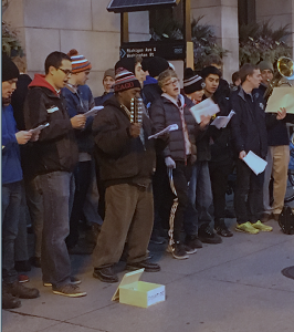Young men are Christmas caroling with the homeless.